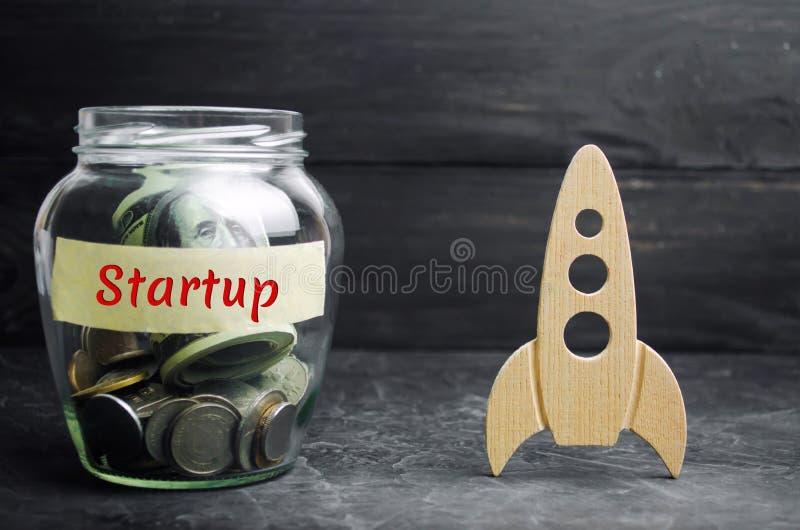 Glaskruik, raket en het woord 'Opstarten ' Het concept het opheffen van fondsen voor een opstarten Liefdadige bijdragen om ideeën royalty-vrije stock foto's
