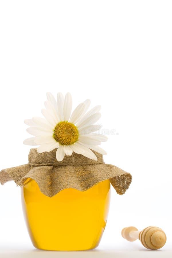 Glaskruik van verse die honing met drizzler en bloemen op witte achtergrond worden geïsoleerd stock afbeelding