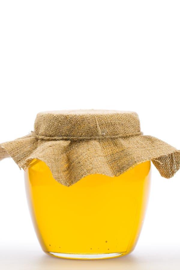 Glaskruik verse die honing op witte achtergrond wordt geïsoleerd royalty-vrije stock foto