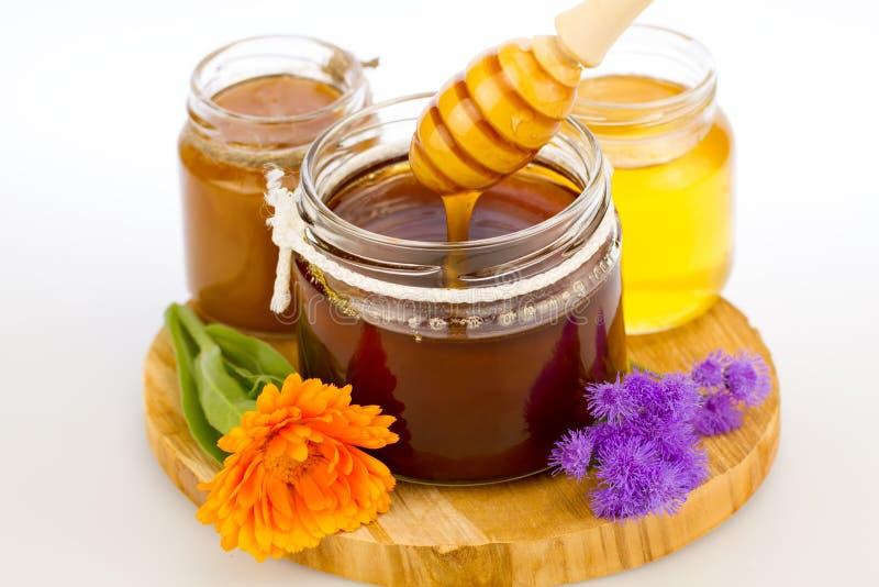 glaskruik verse honing met drizzler en bloemen stock afbeelding