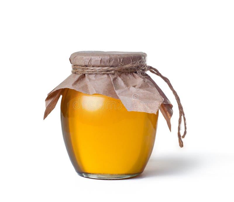 Glaskruik zoete die honing op witte achtergrond wordt geïsoleerd royalty-vrije stock foto