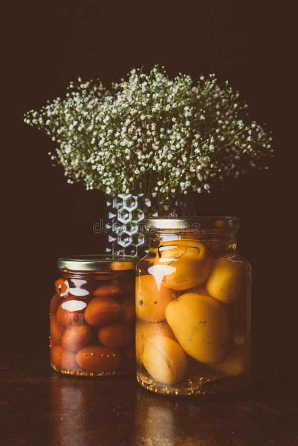 glaskruiken met bewaarde tomaten en bloemen op houten lijst stock foto's
