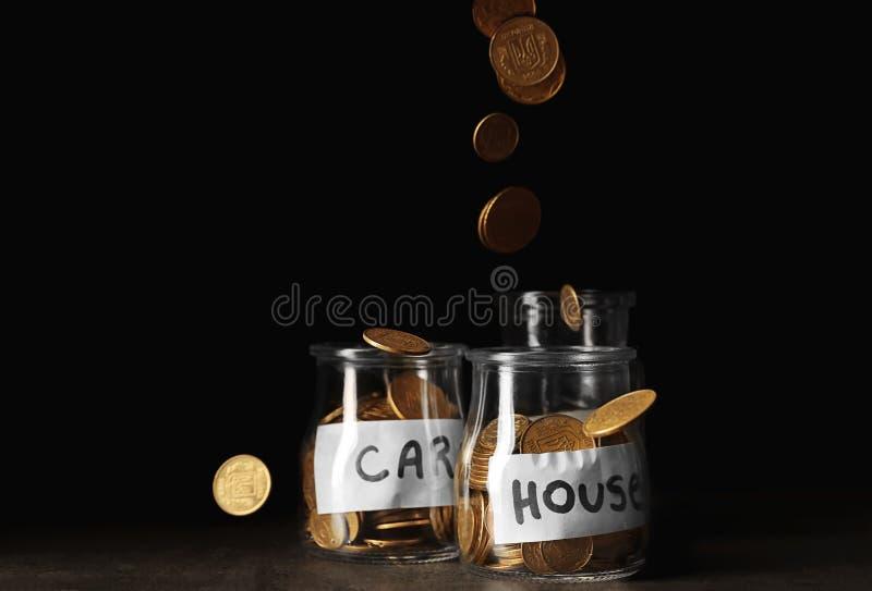 Glaskruiken met muntstukken voor auto en huis op lijst tegen donkere achtergrond royalty-vrije stock fotografie