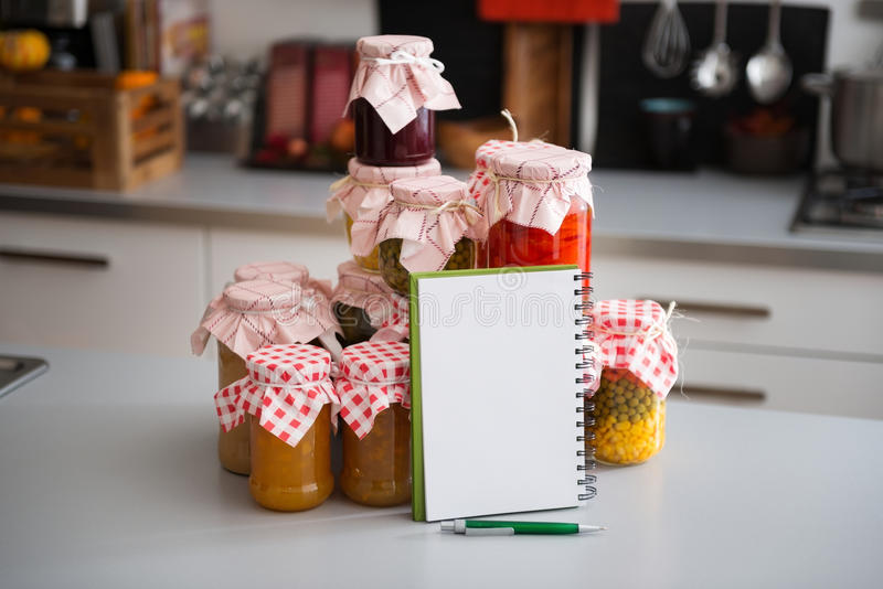 Glaskruiken van bewaarde groenten met notitieboekje en pen stock foto