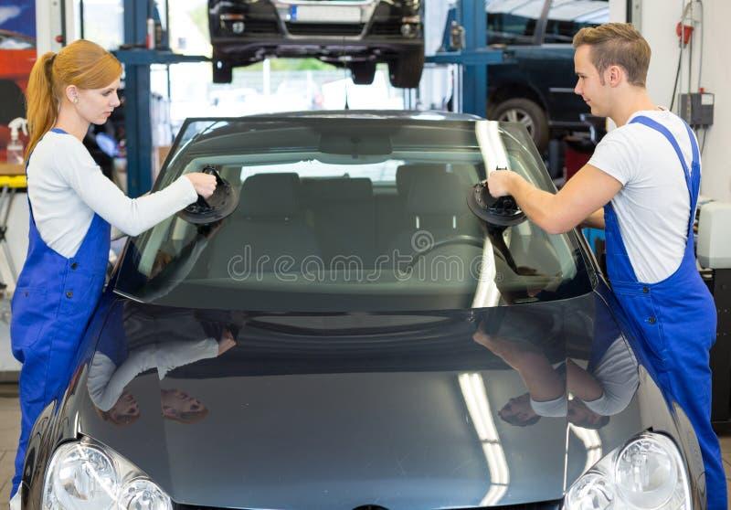 Glasmästare byter ut vindrutan eller vindrutan på bilen, når dehar gå i flisor royaltyfria bilder