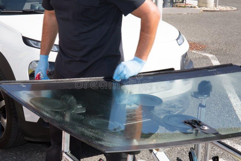 Glasmästare som tar bort vindrutan eller vindrutan på en bil royaltyfria bilder
