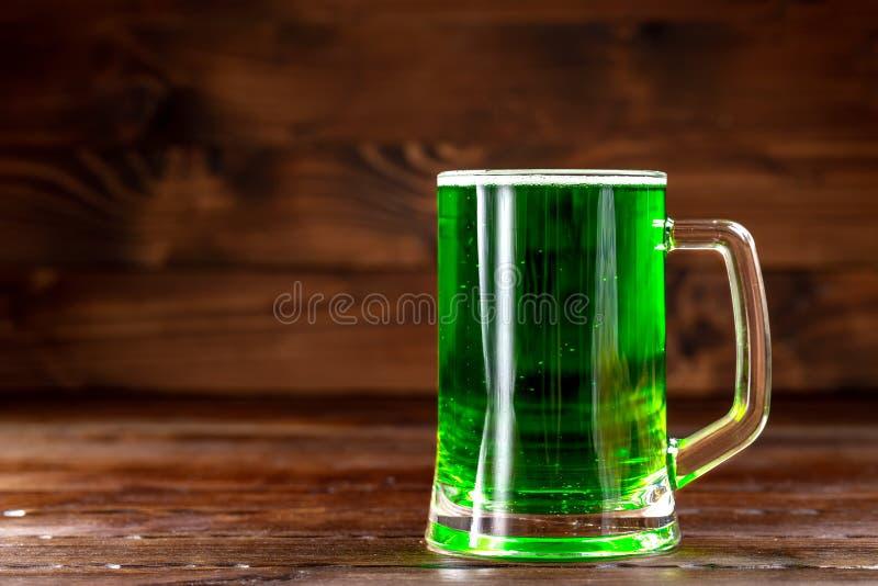 Glasmok met groen bier op een rustieke houten oppervlakte Feestelijke achtergrond voor St Patrick dag Vrije ruimte royalty-vrije stock fotografie