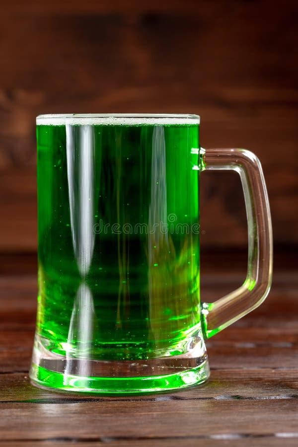 Glasmok met groen bier op een rustieke houten oppervlakte Feestelijke achtergrond voor St Patrick dag Vrije ruimte stock afbeeldingen