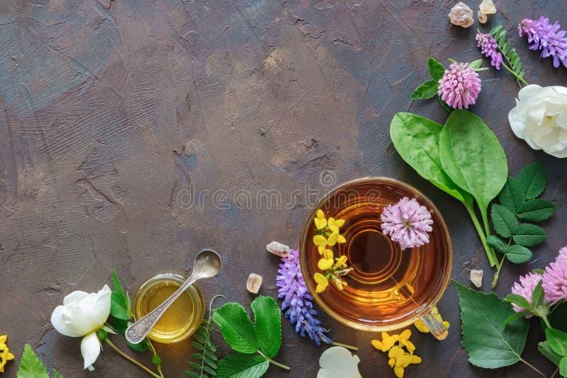 Glasmok van gezond aftreksel, geneeskrachtige kruiden en kleine honingskruik stock foto's