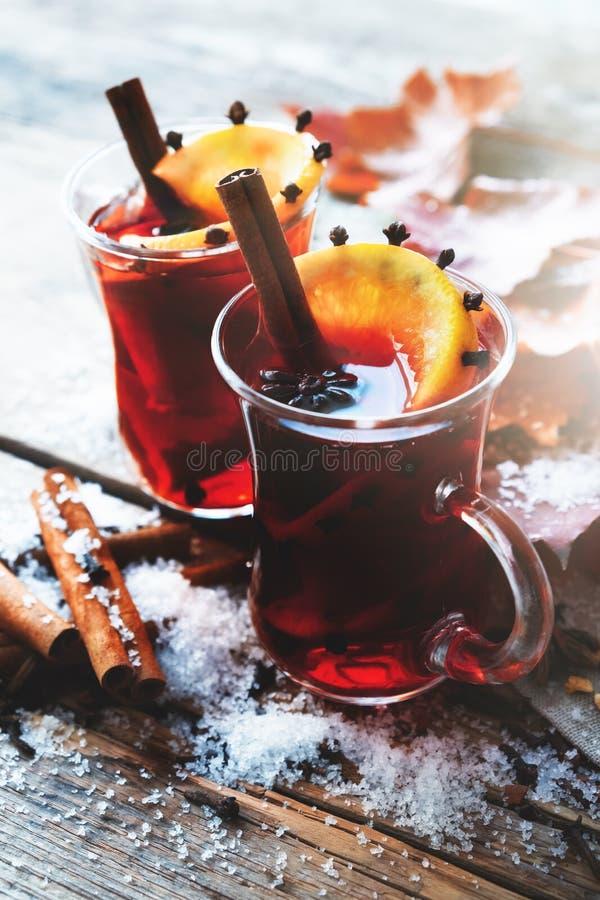 Glasmokken overwogen wijn op lijst met de herfstbladeren en sneeuw stock foto's