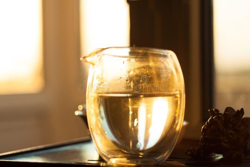 Glaspitcher heißer Tee auf Holztisch auf dem Hintergrund des schönen Sonnenuntergangs mit Sonnenstrahlen stockbild