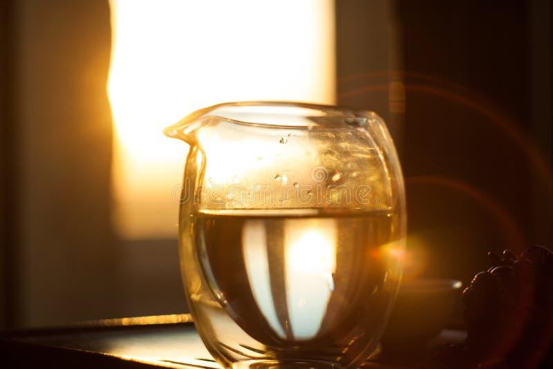 Glaspitcher heißer Tee auf Holztisch auf dem Hintergrund des schönen Sonnenuntergangs mit Sonnenstrahlen lizenzfreie stockfotos