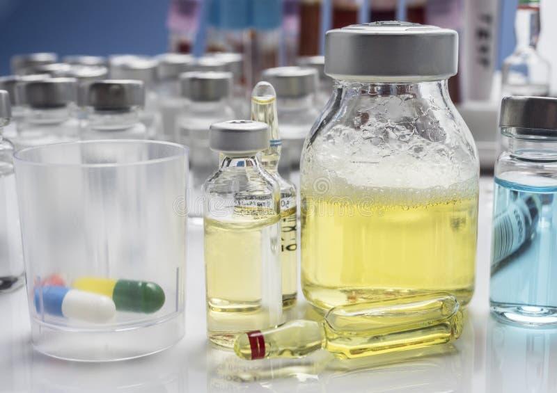 Glasplastik mit Medikationstageszeitung zusammen mit Glasmedizin einiger Phiolen in einem Krankenhaus lizenzfreie stockbilder