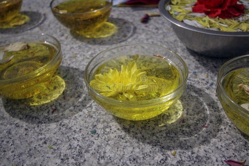 Glasplatten mit Öl und den gelben und roten Blumen lizenzfreies stockfoto