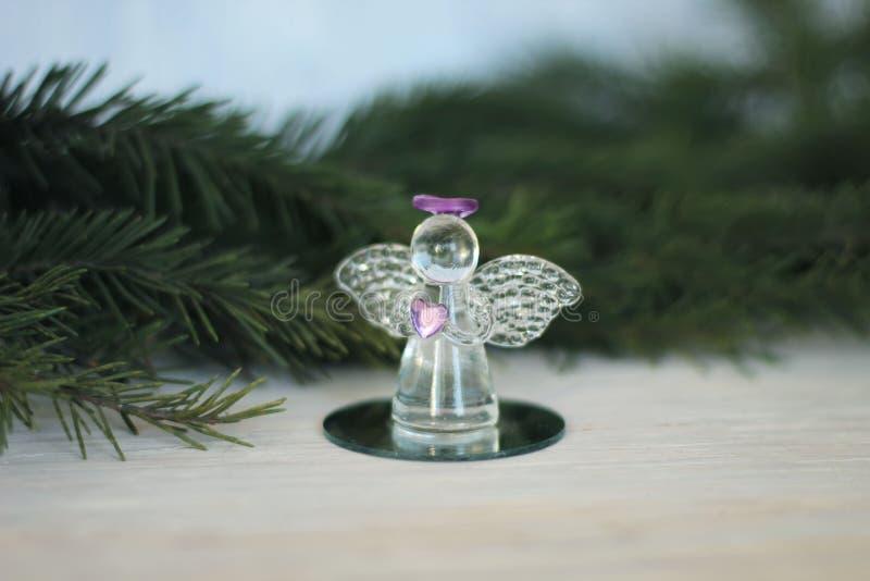 Glass ängelgarnering och julgranfilial arkivfoto