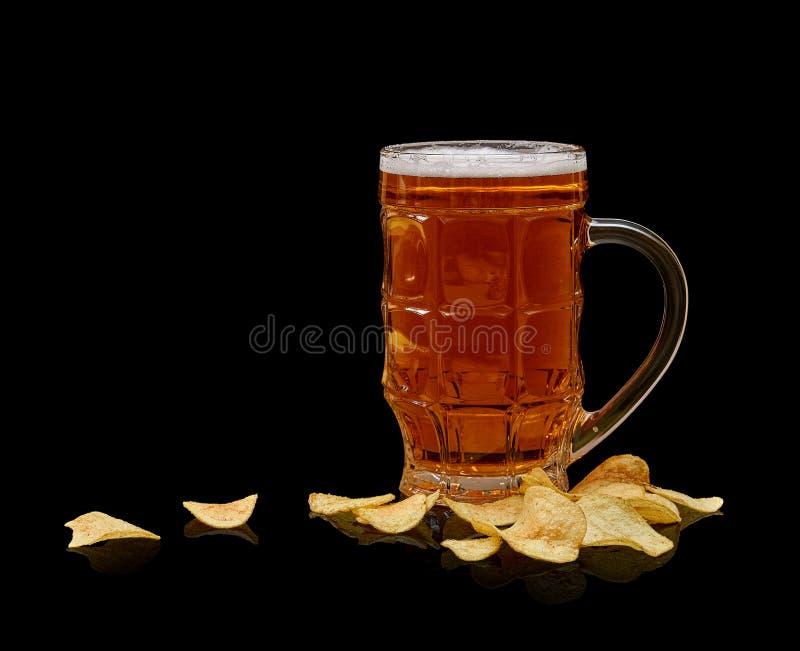 Glass öl rånar med potatischiper som isoleras på svart bakgrund arkivbild