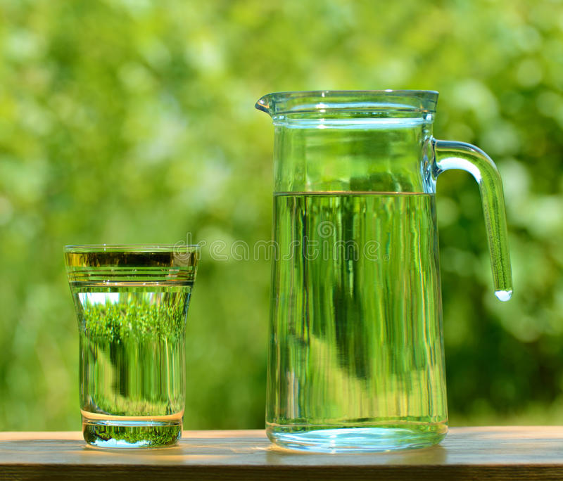 A Glass and а Carafe Full of Water on the Background of Foliage. A Glass and а Carafe Full of Water on a Wooden Table on the Background of Foliage stock photos