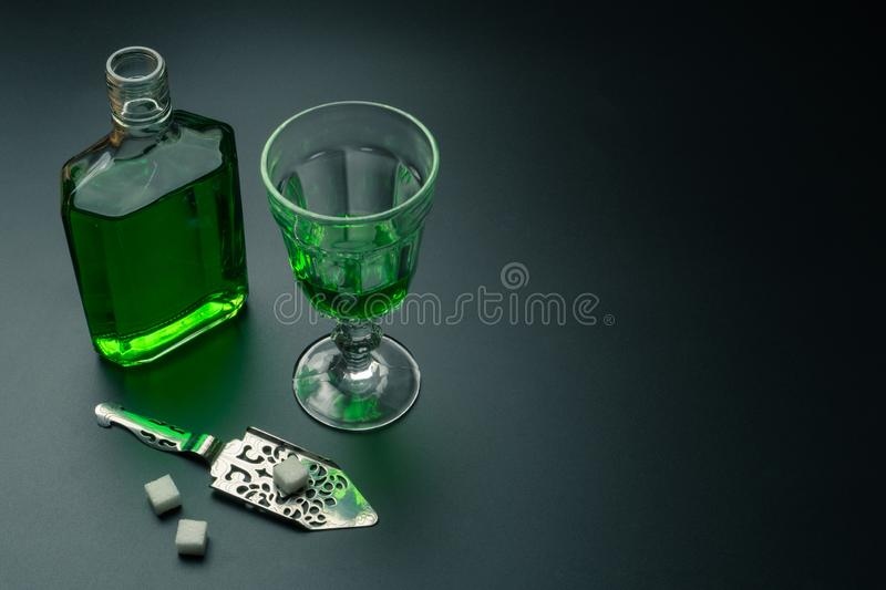 A glass of absinthe, a stainless steel slotted spoon. With the sugar cubes and the absinthe bottle on the table royalty free stock photo