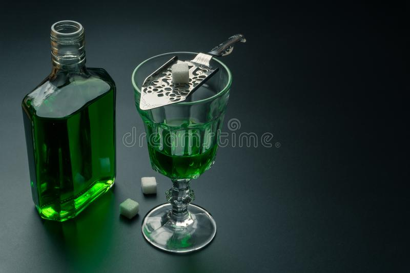 A glass of absinthe and a stainless steel slotted spoon. With the sugar cubes, the absinthe bottle on the table, selective focus royalty free stock photos