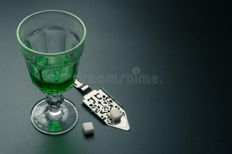 A glass of absinthe and a stainless steel slotted spoon. With the sugar cubes on the table royalty free stock image
