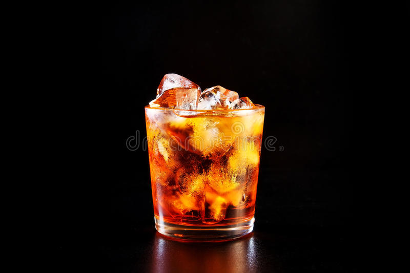 Glass of alcohol on black table royalty free stock image