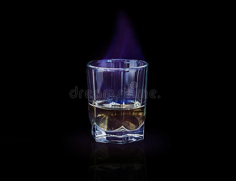 Glass of alcohol burning blue flame royalty free stock image