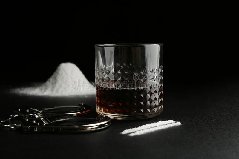 Glass of alcohol, cocaine and handcuffs royalty free stock photos