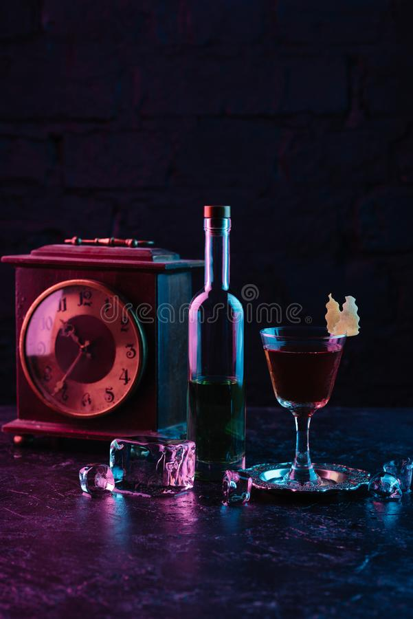 Glass of alcohol cocktail, bottle of liquor and vintage clock. On dark surface royalty free stock photos