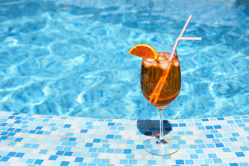 Glass of alcohol cocktail near the pool stock photo