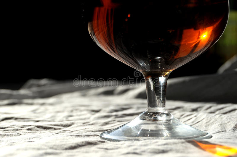 A glass of alcohol drink. On a rough white canvas with a reflection of window in it stock photo