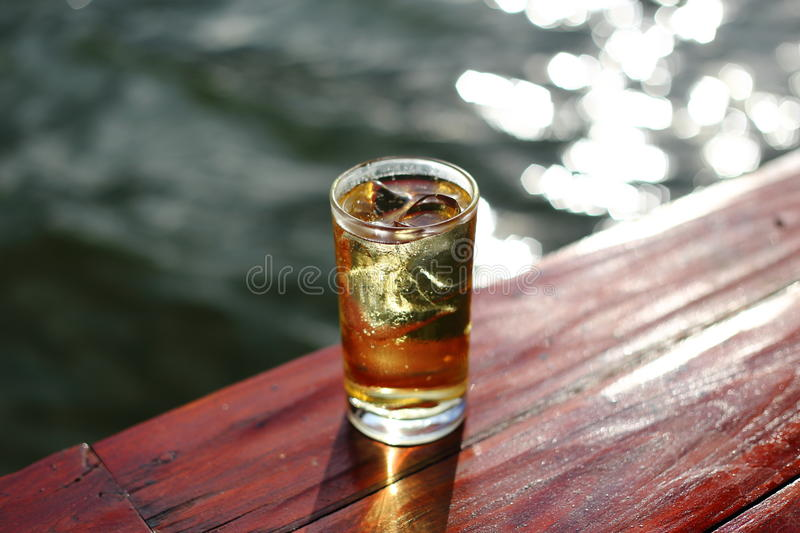 Glass of alcohol with ice beside river. A Glass of alcohol with ice beside river royalty free stock images