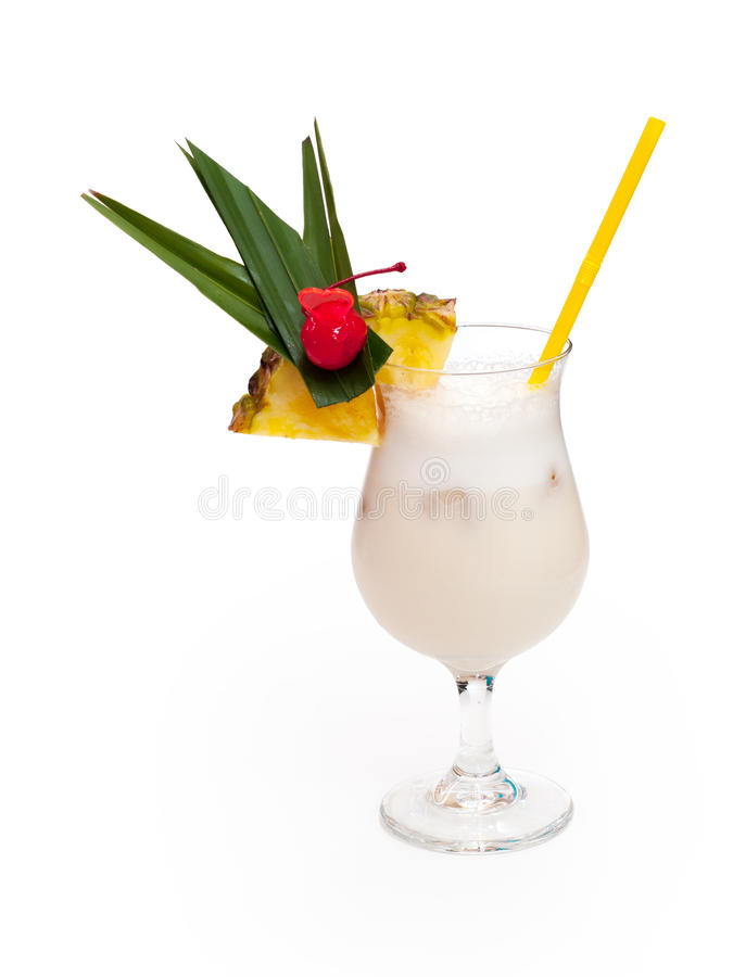 Glass of alcoholic white drink with pineapple, cherry and ice. royalty free stock images
