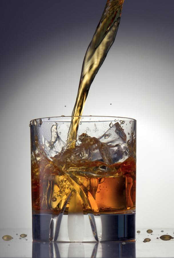 A glass of Anise hit by a wave of liquid royalty free stock photo