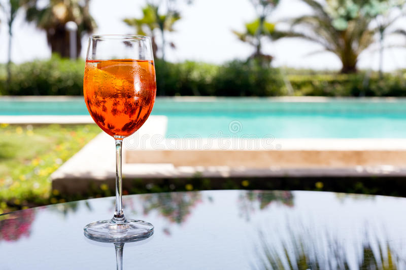 Glass of Aperol Spritz. Cocktail on the glass table in outdoor resort bar royalty free stock photography