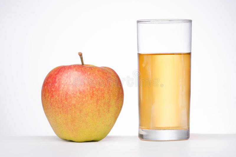 Glass of apple juice and an apple on white background.  royalty free stock photo