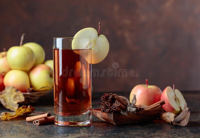 Glass of apple juice with juicy apples and cinnamon sticks on a kitchen table royalty free stock photography