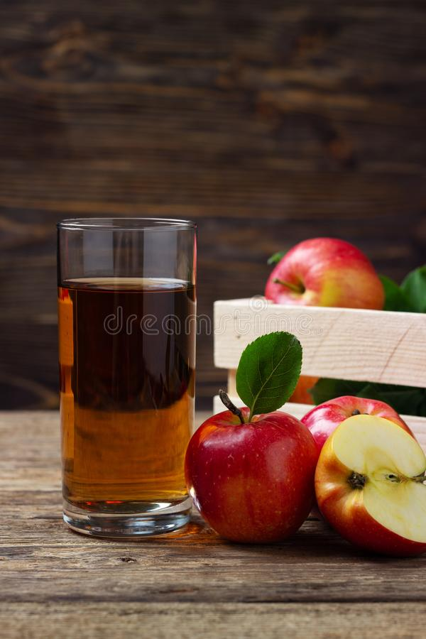 Glass of apple juice with red apples stock photography