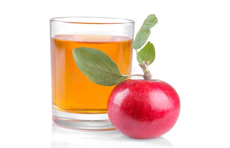 A glass of apple juice with a red ripe apple with leaves on a white isolated background stock image