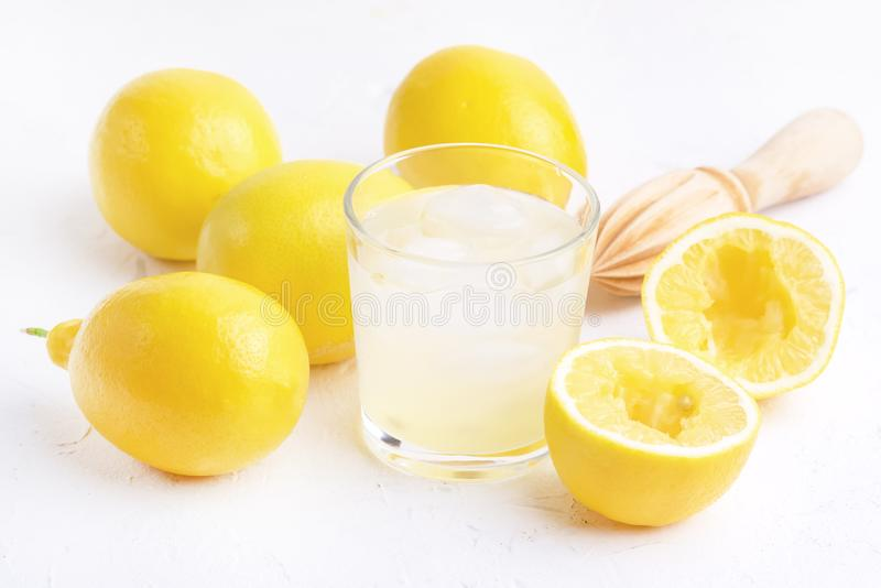 Glass ar of Cold Tasty Fresh Lemonade with Ripe Lemons Wooden Squeezer royalty free stock photo