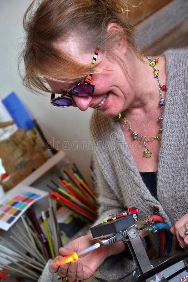 Glass Artist in her workshop. Making beads, wearing protective glasses royalty free stock image