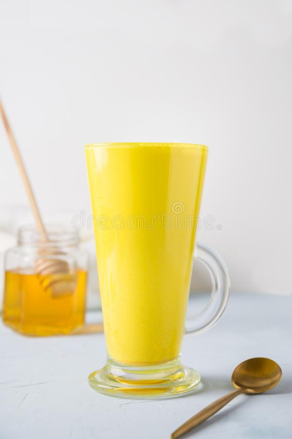 Glass of ayurvedic golden turmeric latte milk with honey, curcuma powder on white royalty free stock images