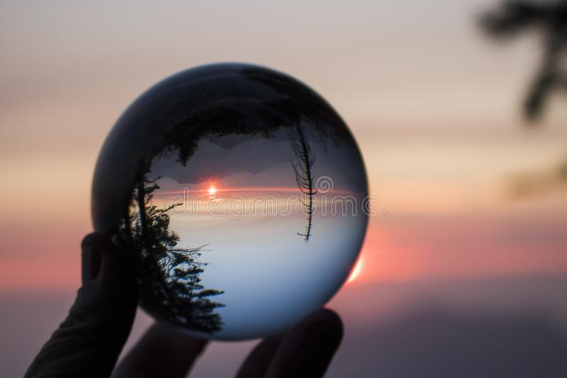 Glass Ball in Fingertips Captures Reflection of Sunset over Sierra Nevada Mountain Range with Forest Trees in Silhouette royalty free stock photography