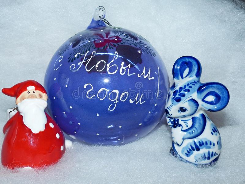 Glass ball with the inscription in Russian `Happy New Year`, Santa Claus and symbol of the New Year 2020 is a white rat. Glass ball with the inscription in royalty free stock photography