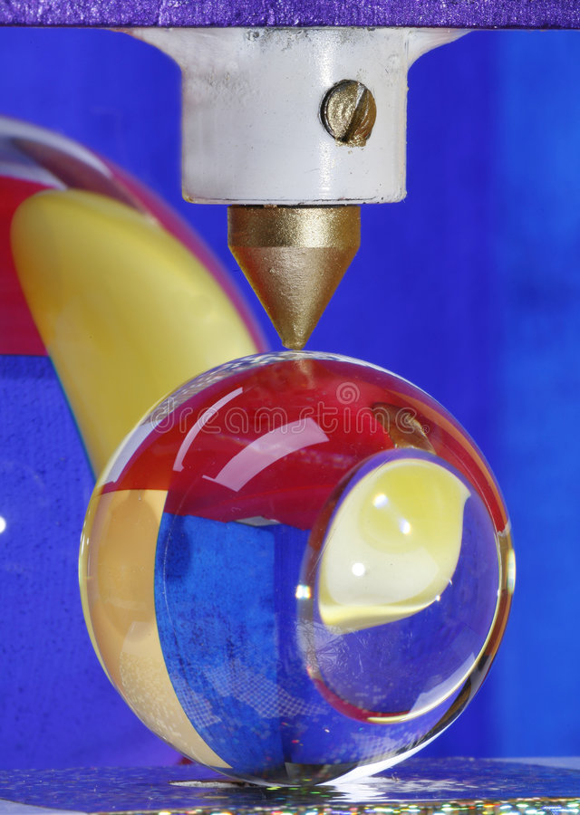 Glass ball under machine press. Ball of glass held by the point of a machine press used to shatter stones. In the background is a partial view of a bigger ball royalty free stock images