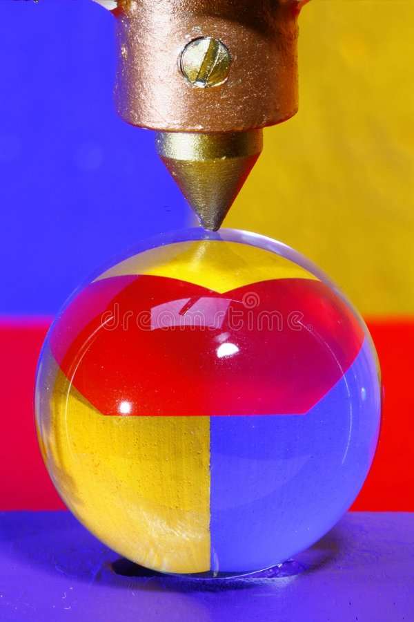Glass ball under sharp point. Ball of glass in a press used to smash stones. Background of several colours is reflected in it stock image