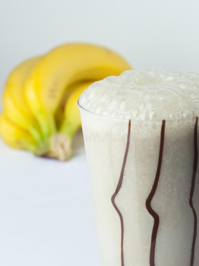 A glass of banana and milk cocktail close up with full fruits stock photos