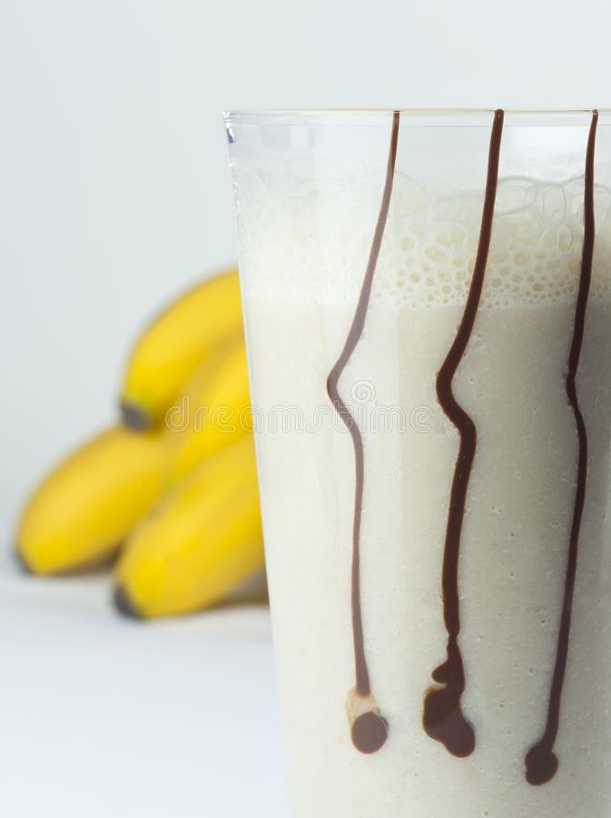 A glass of banana and milk cocktail close up with full fruits royalty free stock images