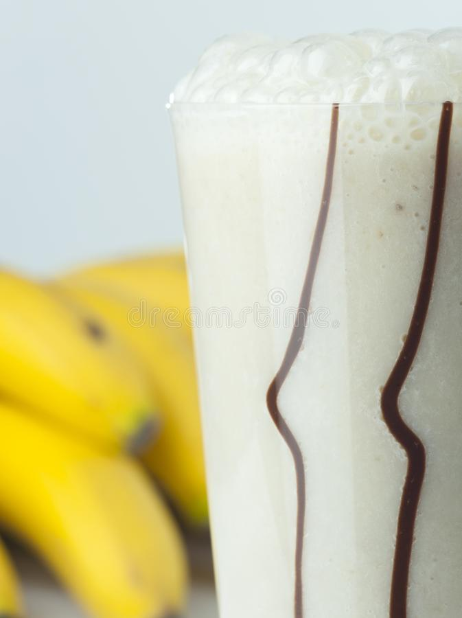 A glass of banana and milk cocktail close up with full fruits stock photography