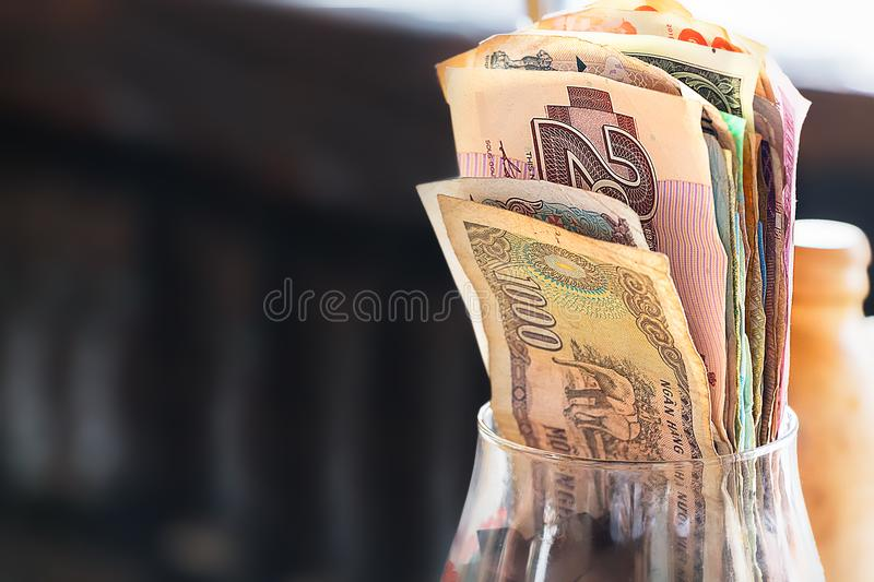 Glass with banknotes closeup, indoors. A glass with banknotes for tips, saving concept, closeup, indoors royalty free stock images