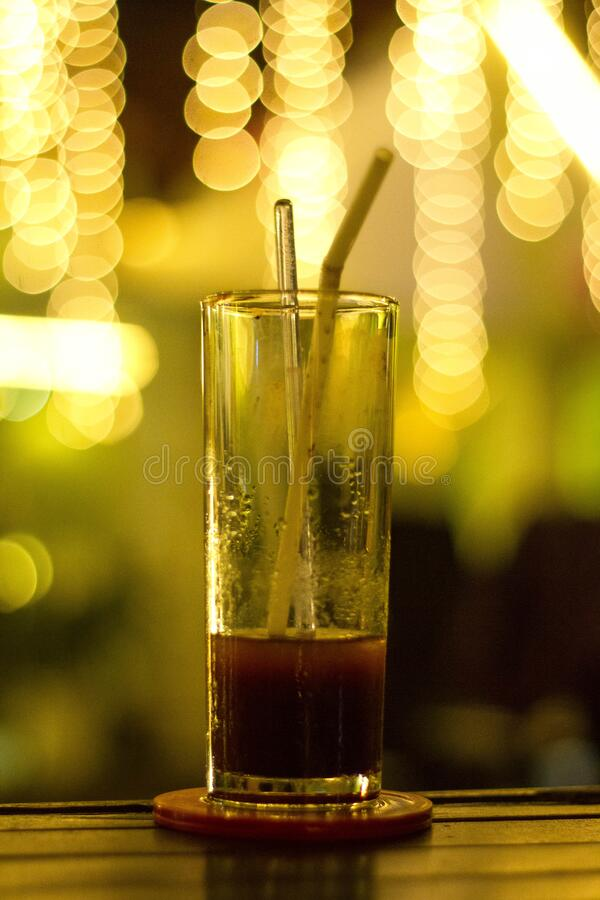 Glass on bar with red beverage royalty free stock photos